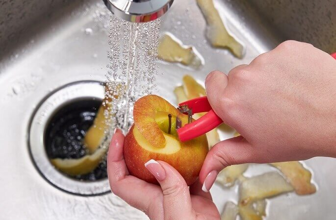 garbage disposal with running water and person peeling apple into kitchen sink